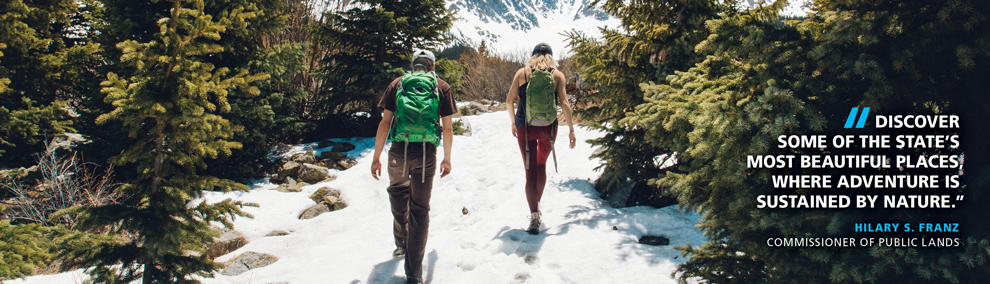 Hikers on a trail. Commissioner of Public Lands Hilary Franz quote: Discover  some of the state's most beautiful places, where adventure is  sustained by nature.